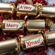 Merry Xmas ! Christmas Crackers - with red, gold, silver tinsel. — Stock Photo