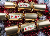 Merry Xmas ! Christmas Crackers - with red, gold, silver tinsel. — Stockfoto