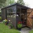 Garden shed exterior with door open, tools, flowers and plants. — Photo #46133533