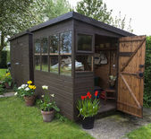 Garden shed exterior with door open, tools, flowers and plants. — Stock Photo