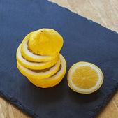 Lemon and lemon slices, juicy and ripe, on slate. — Stock Photo