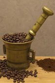 Grains of coffee in a bronze mortar — Stock Photo