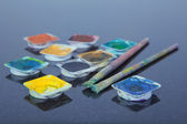 Brushes laying on different paint pots — Stock Photo