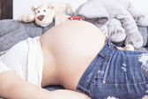 Pregnant belly with red toy car on the top — Stock Photo
