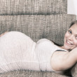 Pregnant Girl is laying on a sofa — Stock Photo