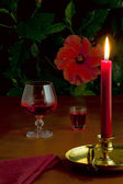 A glass of red wine, a small glass with liquor and a burning candle — Stock Photo