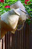 Old jugs on a rustic fence — Stock Photo