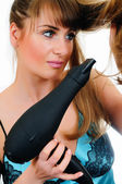 Young woman with a hair drier — Stock Photo