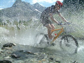 Mountain biker riding through river bed — Stock Photo