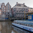 Постер, плакат: Tour boat and canal houses in Amsterdam