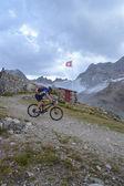 Mountain biker riding though Swiss mountain area — Stock Photo