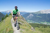 Mountain biker riding downhill in Swiss Alps — Stock Photo