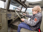 Kid at the wheel of a military vehicle — Stock Photo