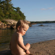Stock Photo: Toddler playing with stick at beach