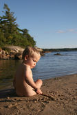 Toddler playing with stick at beach — Stock Photo