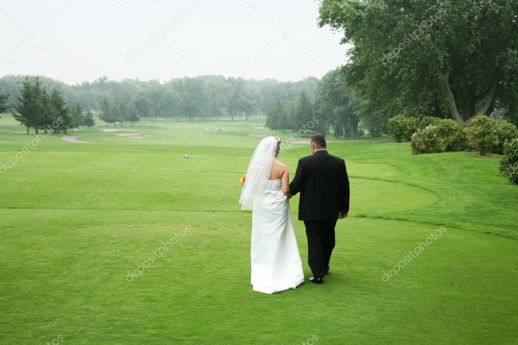 Wedding couple walking at a golf course — Stock Photo #20144889