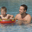 Father and son having fun in outdoor swimming pool - Stockfoto