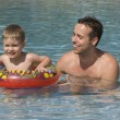 Father and son having fun in outdoor swimming pool - Stok fotoğraf