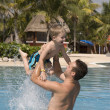 Father and son playing in outside swimming pool at a tropical re - Stockfoto