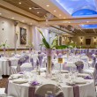Indoor wedding reception hall with round tables and floral cent — Stock Photo
