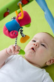 Baby looking up at a mobile toy — Stock Photo