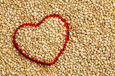 Red heart shape on uncooked quinoa background — Stock Photo