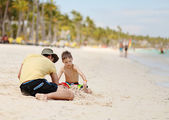 Caucasian boy and father playing with sand at tropical beach — Stock Photo