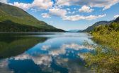 Klidné jezero s nadýchaný mrak reflexe — Stock fotografie