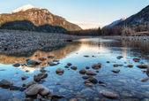 Río conduce hacia el poniente iluminado montañas — Foto de Stock