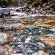 closeup rocks in clear water stream — Stock Photo
