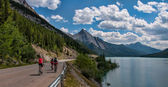 Three Cyclists On Road With Mountains — Stock Photo