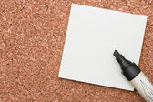 Black marker with white sticky note on cork — Stock Photo