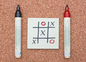 Tic tac toe game with red and black markers on cork — Stock Photo