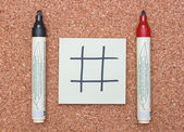 Blank tic tac toe game on sticky note with red and black markers — Stock Photo