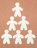 Pyramide of white paper man on recycle paper — Stock Photo