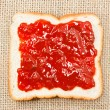 Slice of bread with strawberry jam on sacking background — Stockfoto