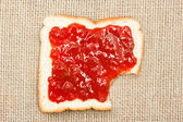 Bite out of a slice of bread with strawberry jam on sacking — Stock Photo