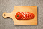 Sliced tomato on wooden cutting board with sacking — Стоковое фото