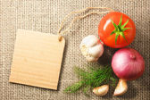 Tomato onion and garlic vegetables and price tag on sacking back — Stock Photo
