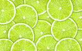 Close-up green background with lime slices — Stock Photo