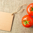 Royalty-Free Stock Photo: Two tomatoes with cardboard tag on sacking