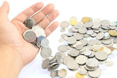Hand releasing coins over white background — Foto de Stock