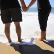 Couple holding hands at a beach — Stock Photo