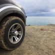 Dirty SUV car tire with gloomy sky — Stock Photo