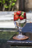 Strawberries in a glass beside a pool — Stock Photo