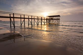 Sunset with silhouette of a wooden jetty at a beach in Sabah, Malaysia, Borneo — Stock Photo