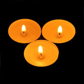 Three candles triangle on a black background — Stock Photo
