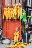 Stack of yellow umbrellas for sale at a stall — Stock Photo