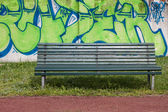 Green bench with graffiti on the background — Stock Photo