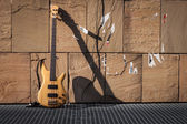Bass guitar against a wall — Stockfoto